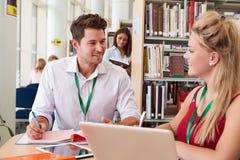 Insegnante Helping College Student con gli studi in biblioteca immagine stock