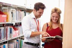 Insegnante Helping College Student con gli studi in biblioteca fotografia stock libera da diritti
