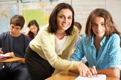 Insegnante Helping Female Pupil che studia allo scrittorio in aula Fotografia Stock