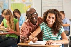 Insegnante Helping Female Pupil che studia allo scrittorio in aula Immagini Stock Libere da Diritti