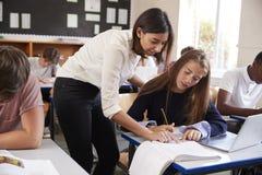 Insegnante Helping Female Pupil che utilizza computer nell'aula fotografie stock libere da diritti