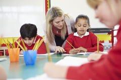 Insegnante Helping Female Pupil con la lettura di scrittura allo scrittorio fotografia stock