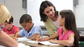 Insegnante Helping Female Pupil nella classe video d archivio