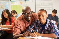 Insegnante Helping Male Pupil che studia allo scrittorio in aula Immagini Stock