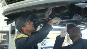 Insegnante Helping Male Student che si prepara per essere meccanico di automobile archivi video