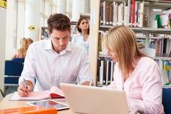 Insegnante Helping Mature Student con gli studi in biblioteca fotografia stock libera da diritti