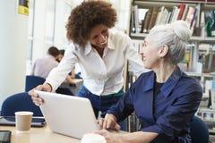 Insegnante Helping Mature Student con gli studi in biblioteca immagini stock