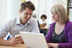 Insegnante Helping Mature Student con gli studi in biblioteca immagine stock libera da diritti