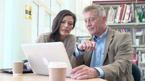 Insegnante Helping Mature Student con gli studi in biblioteca stock footage