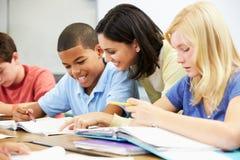 Insegnante Helping Pupils Studying agli scrittori in aula immagini stock libere da diritti