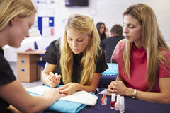 Insegnante Helping Students Training da trasformarsi in in estetisti fotografia stock