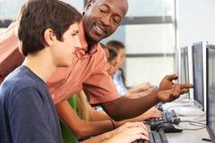 Insegnante Helping Students Working ai computer in aula immagini stock libere da diritti