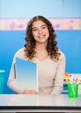 Insegnante Holding Book While che si siede allo scrittorio Immagine Stock