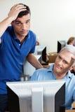 Insegnante irritato With Senior Man che utilizza computer nella classe Fotografia Stock