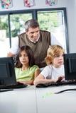 Insegnante Looking At Schoolchildren che usando desktop pc Immagini Stock Libere da Diritti
