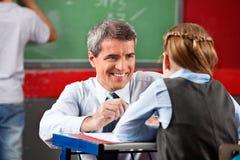 Insegnante Looking At Schoolgirl che si siede allo scrittorio Fotografie Stock