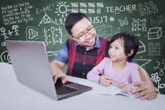 Insegnante maschio che aiuta il suo studente ad imparare Immagine Stock