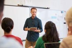 Insegnante maschio che per mezzo del computer della compressa alla classe di corsi per adulti Immagini Stock Libere da Diritti