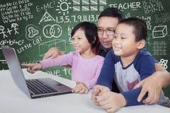 Insegnante maschio ed i suoi studenti che per mezzo del computer portatile Fotografia Stock Libera da Diritti