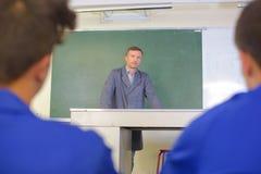 Insegnante nei sudents anteriori di retrovisione due della lavagna fotografie stock libere da diritti