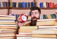 Insegnante o studente con la barba che studia nella biblioteca Uomo, scienziato che dà una occhiata dai mucchi dei libri con la s Fotografie Stock Libere da Diritti