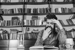 Insegnante o studente con la barba che studia nella biblioteca Uomo sul libro di lettura di sbadiglio del fronte, studiante, scaf Immagini Stock Libere da Diritti