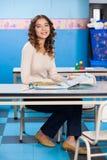 Insegnante With Popup Book che si siede allo scrittorio dentro Immagine Stock