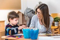 Insegnante prescolare con il bambino all'asilo - Art Class creativo immagini stock
