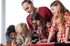Insegnante professionista ammirevole che assiste i suoi studenti Fotografia Stock