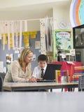 Insegnante Sitting With Boy che utilizza computer portatile nella classe Fotografie Stock