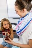 Insegnante sorridente che assiste ragazza per giocare violino in aula fotografia stock libera da diritti