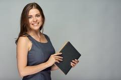 Insegnante sorridente con il libro che sta contro il gray Immagini Stock