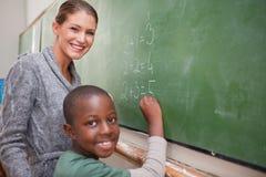 Insegnante sorridente e un allievo che fa un'aggiunta Fotografie Stock Libere da Diritti