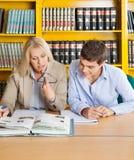 Insegnante And Student Looking al libro mentre sedendosi Fotografie Stock Libere da Diritti