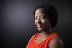 Insegnante sudafricano o afroamericano della donna sul fondo del bordo del nero del gesso Fotografia Stock