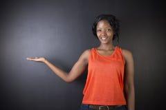 Insegnante sudafricano o afroamericano della donna sul fondo del bordo del nero del gesso Fotografia Stock Libera da Diritti