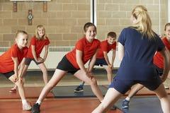 Insegnante Taking Exercise Class nella palestra della scuola Immagini Stock