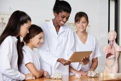 Insegnante With Teenage Girls che per mezzo della compressa di Digital a Immagini Stock