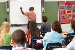 Insegnante Using Interactive Whiteboard durante la lezione Fotografia Stock