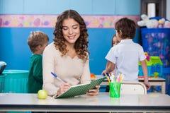 Insegnante Writing In Book Immagine Stock