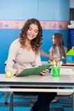 Insegnante Writing In Book Fotografia Stock Libera da Diritti