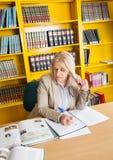Insegnante Writing In Book alla biblioteca universitaria Fotografie Stock Libere da Diritti