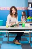 Insegnante Writing In Book con la ragazza che gioca dentro Fotografia Stock Libera da Diritti