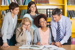 Insegnanti che discutono con gli studenti nella biblioteca Fotografia Stock Libera da Diritti