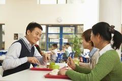 Insegnanti che parlano al pranzo nel self-service di scuola Fotografia Stock Libera da Diritti