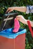 Insegua il proprietario che mette la borsa della poppa nel recipiente sulla passeggiata Immagini Stock