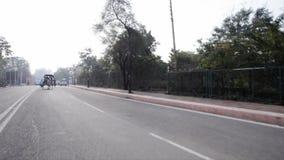 Inseguimento del colpo dei carretti del cavallo che passano la strada, Agra, Uttar Pradesh, India archivi video