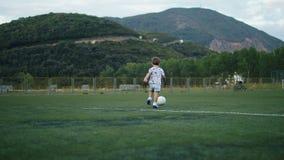 Inseguimento della macchina fotografica di un ragazzino che segna uno scopo nel campo di football americano video d archivio