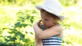 Insektencreme Moskitocreme sonnenbrand suncream Sonnenschutzcreme Nahaufnahmegesichtsbaby Kind schmiert seinen Körper stock footage