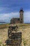 Insel des Leuchtturmes mit Felsen Stockbild